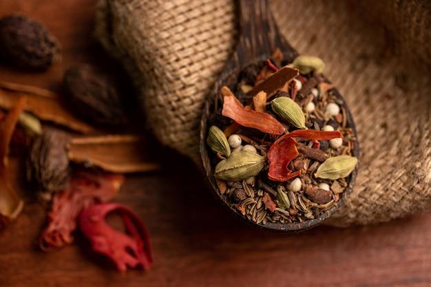 Mescola le spezie e le erbe in un cucchiaio di legno sulla superficie scura, sulle spezie indiane e sugli ingredienti della cucina