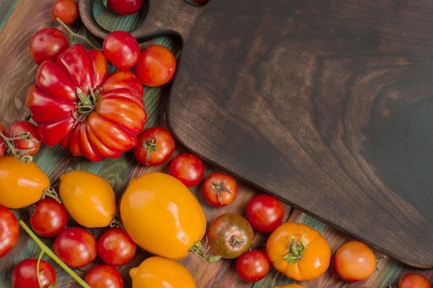 Mescolare la priorità bassa dei pomodori. diverse varietà di pomodori in giornata estiva. diversi tipi di pomodori colorati assortiti.
