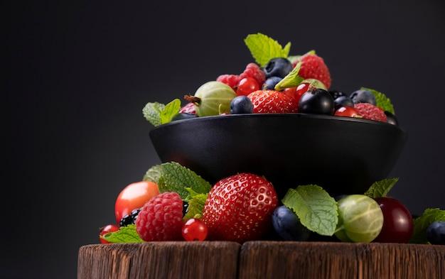 Mix di frutti di bosco su nero, raccolta di fragole, mirtilli, lamponi e more