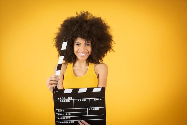 Misto afroamericano giovane donna, eccitato, abbigliamento casual, tenendo la bocca aperta tenere premuto classico film nero ciak isolato su sfondo arancione.