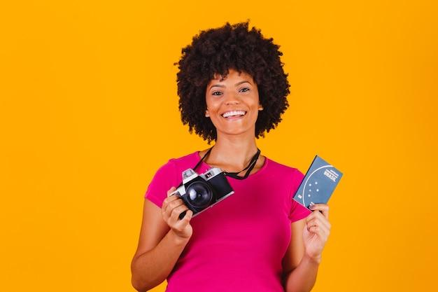 Donna afro mista con una fotografia con fotocamera e passaporto brasiliano