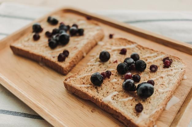 Fette biscottate ai frutti di bosco servite su piatto di legno