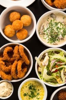 Spuntini brasiliani misti, inclusi pasticcini, pollo fritto, insalate, zuppe, patatine fritte e kibe