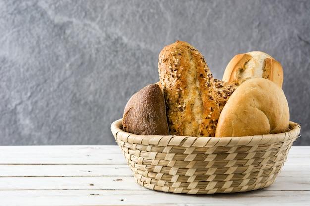 Merce nel carrello mista del pane sulla tavola di legno bianca