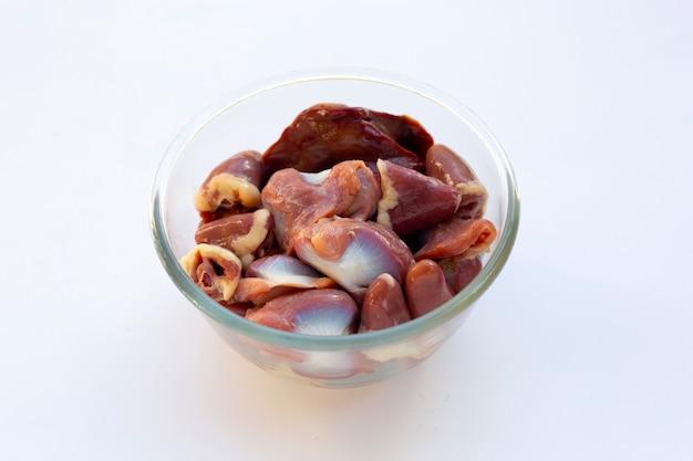 Interiora di pollo miste in ciotola di vetro su fondo bianco.