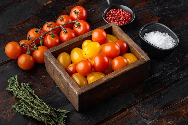 Pomodorini di colore misto in vassoio di legno, sulla vecchia tavola di legno
