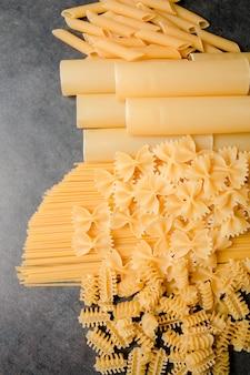 Selezione di pasta secca mista su sfondo nero. varietà di tipi e formati di pasta italiana. sfondo di pasta cruda.