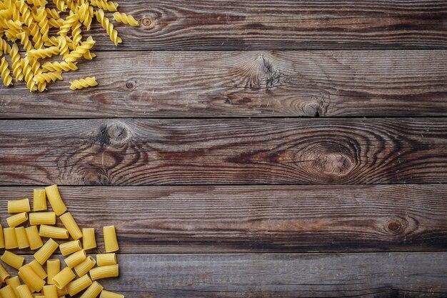 Selezione di pasta secca mista su fondo di legno. vista dall'alto piatta con copyspace per testo, logo o altro.