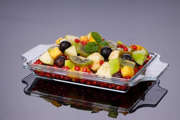 Macedonia di frutta mista disposta in stoviglie rettangolari trasparenti e guarnita con foglioline di menta.