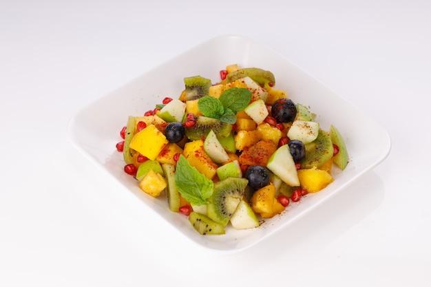 Macedonia di frutta mista disposta in un vasetto bianco e guarnita con foglia di menta.