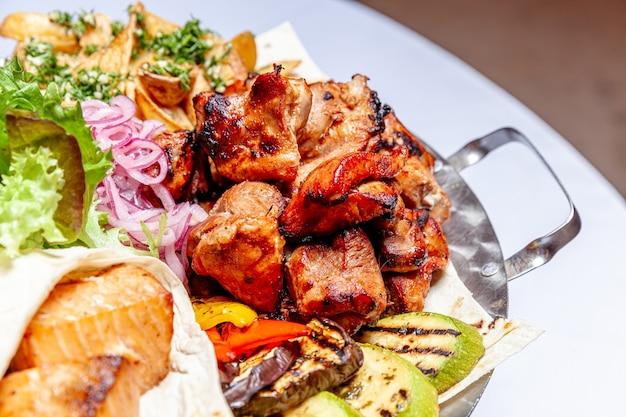 Grigliata mista di carne, verdure fritte e decorazione di filetti di salmone alla griglia in piatto caldo
