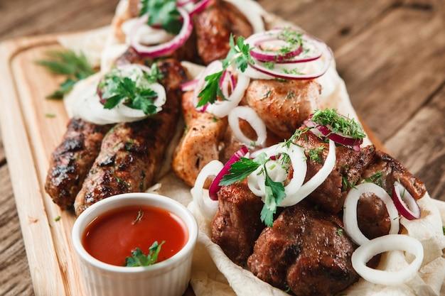 Piatto misto di carne alla griglia. carne alla griglia deliziosa assortita servita su pane pitta con erbe aromatiche, cipolla e salsa di pomodoro, primo piano.