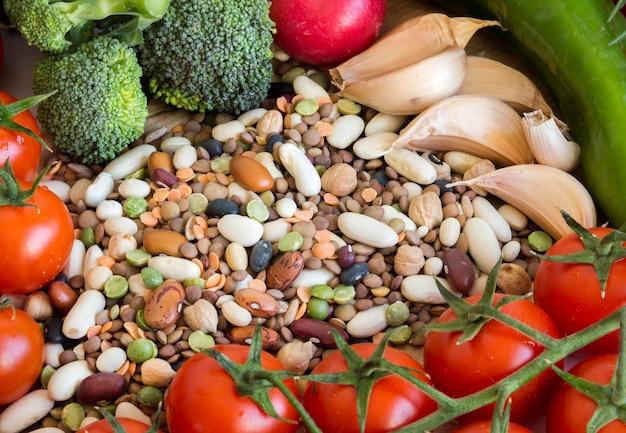 Legumi misti e verdure crude su una fine di legno marrone della tavola su