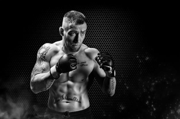 Combattente di arti marziali miste in posa su uno sfondo di griglia metallica. concetto di mma, ufc, thai boxe, boxe classica. tecnica mista