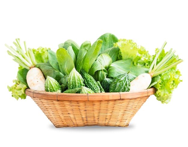 Raccolta di verdure biologiche miste nel cesto intrecciato su sfondo bianco