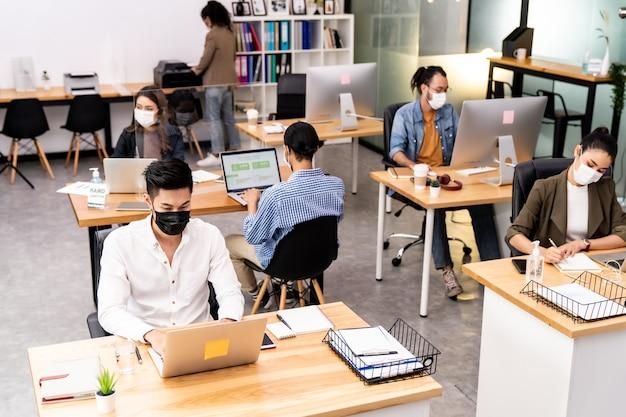 Razza mista di uomini d'affari africani e asiatici che indossano maschere facciali in ufficio