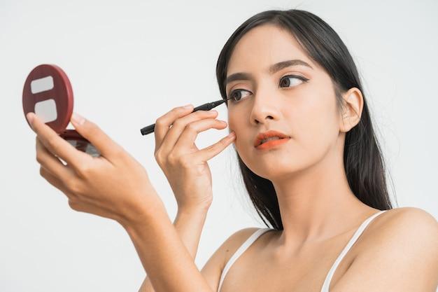 Donna asiatica di razza mista che mette eye liner sulla palpebra sul muro bianco