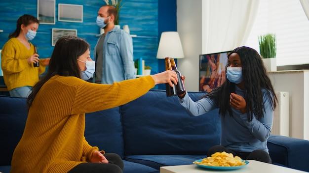 Donna nera di razza mista che si toglie maschere di protezione tintinnando bottiglie di birra, bevendo e mangiando snack trascorrendo il tempo libero in soggiorno rispettando la distanza sociale. diverse persone che si godono la festa in o