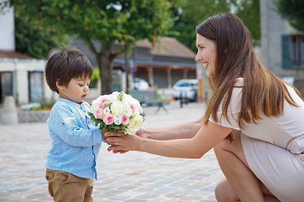 Ragazzo di razza mista, piccolo figlio che si congratula con sua madre e le dà un bouquet di fiori, si abbracciano e ridono insieme. concetto di vacanze in famiglia