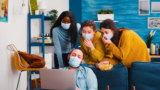 Amici allegri di razza mista che guardano nel laptop una clip divertente seduta in soggiorno con maschere protettive mantenendo le distanze sociali per prevenire la diffusione del coronavirus