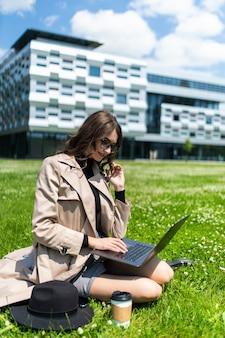Studente di college di razza mista seduto sull'erba che lavora al computer portatile al campus