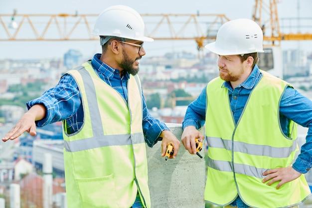 Ingegnere di costruzione della corsa mista che parla con collega