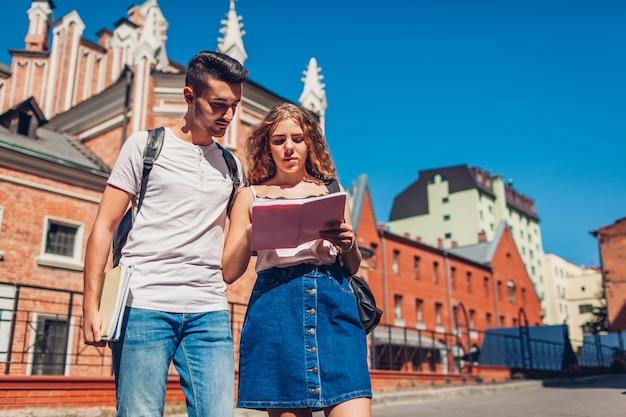 Razza mista coppia di studenti universitari a piedi dall'università con i quaderni. giovane uomo arabo e donna bianca che studiano all'aperto