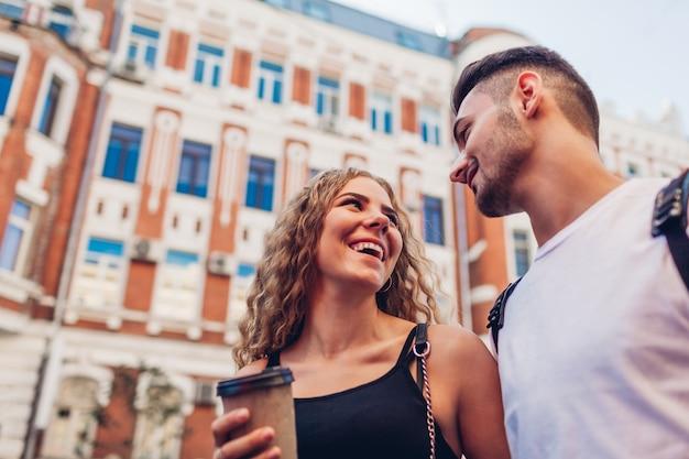 Coppia di razza mista innamorata che cammina in città. uomo arabo e donna bianca che bevono caffè, parlano e ridono all'aperto