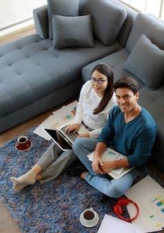 Famiglia di razza mista, marito caucasico e moglie asiatica, uomini d'affari seduti e che lavorano insieme in soggiorno con laptop e tazza di caffè. idea di lavoro a casa.