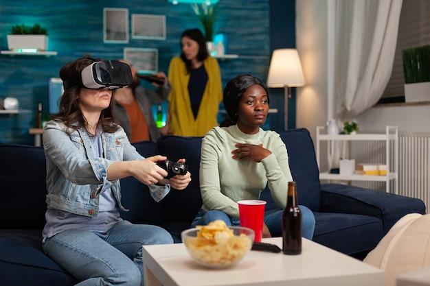 Amici di razza mista che hanno una competizione di giochi virtuali online indossando l'auricolare vr, utilizzando il controller wireless, uscire a tarda sera seduti sul divano a bere birra e gustare snack.