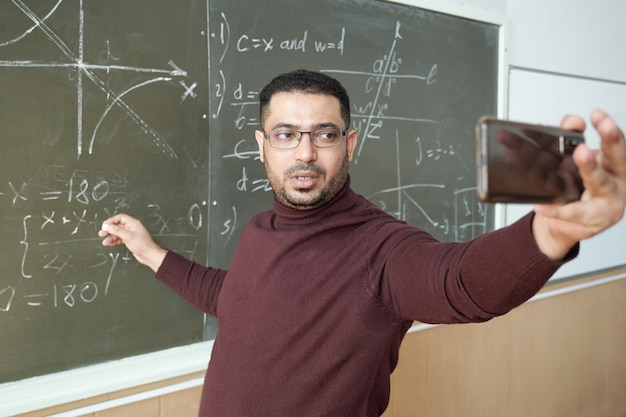 Uomo di razza mista in abbigliamento casual che tiene lo smartphone davanti a sé mentre è in piedi vicino alla lavagna e spiega come risolvere l'equazione