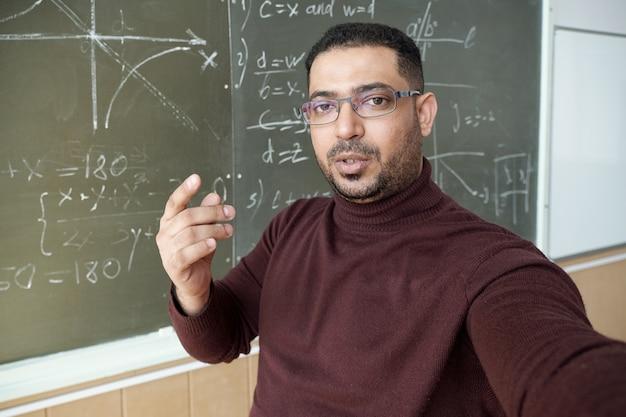 Uomo di razza mista che tiene lo smartphone davanti a sé e ti guarda mentre è in piedi vicino alla lavagna e spiega come risolvere l'equazione