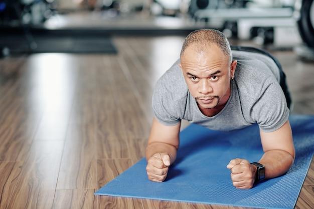 Uomo maturo di razza mista che fa posizione della plancia durante l'allenamento in palestra