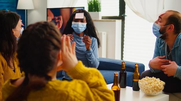 Razza mista di persone con note adesive sulla fronte che giocano a giochi di nome divertendosi con birra e popcron mantenendo il distanziamento sociale. con mascherina per prevenire la diffusione del covid19 nel soggiorno di casa.
