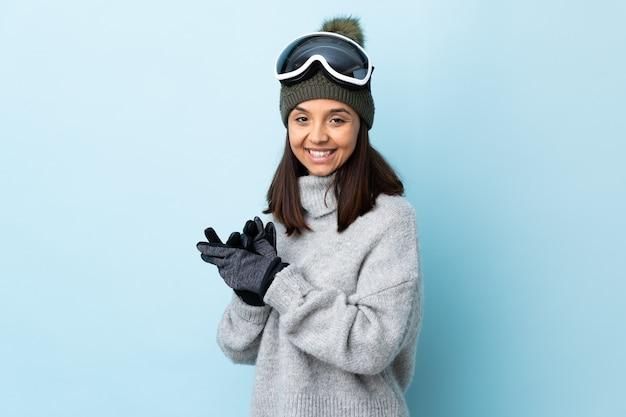 Ragazza di sciatore di razza mista con occhiali da snowboard su sfondo blu isolato che applaude.