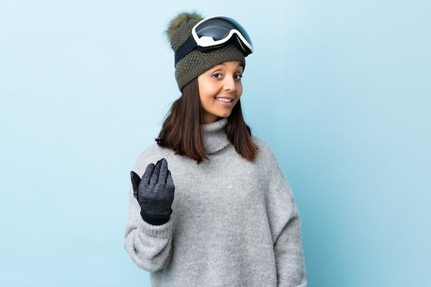 Ragazza di sciatore di razza mista con occhiali da snowboard su sfondo blu isolato che invita a venire con la mano. felice che tu sia venuto.