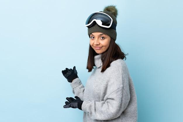 Ragazza di sciatore di razza mista con occhiali da snowboard sulla parete blu isolata che estende le mani di lato per invitare a venire.