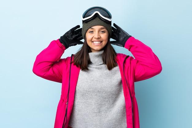Ragazza di sciatore di razza mista con occhiali da snowboard sopra la risata blu isolata della parete.