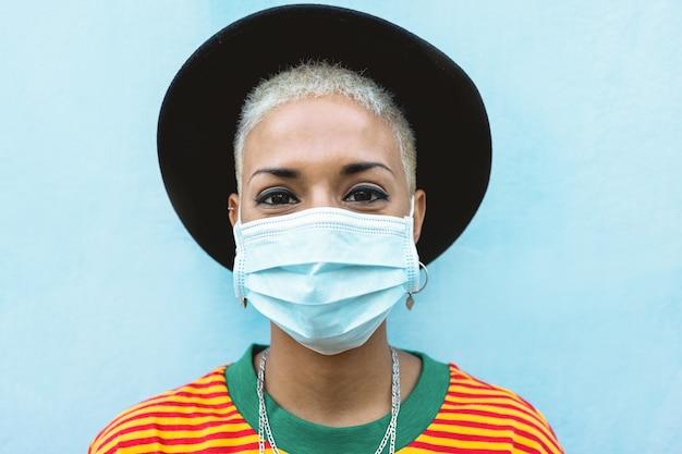 Razza mista sorridente che indossa una maschera protettiva per il viso durante l'epidemia di coronavirus