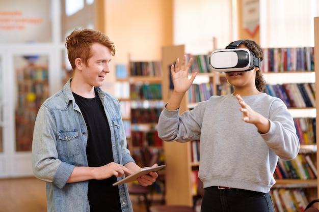 Studente di razza mista con auricolare vr e il suo compagno di classe con touchpad che discutono i punti della presentazione in biblioteca