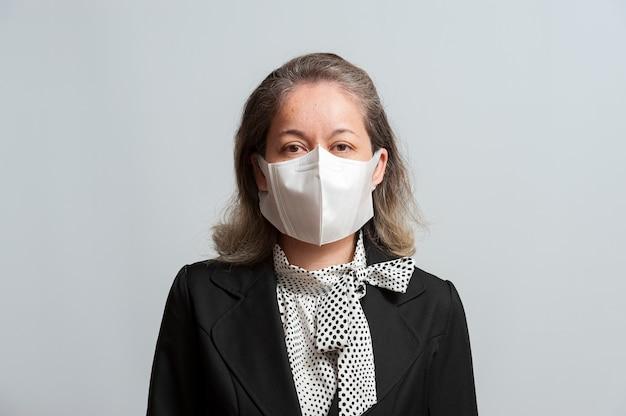 Donna di razza mista in abbigliamento formale che indossa una maschera chirurgica bianca per la protezione contro covid19