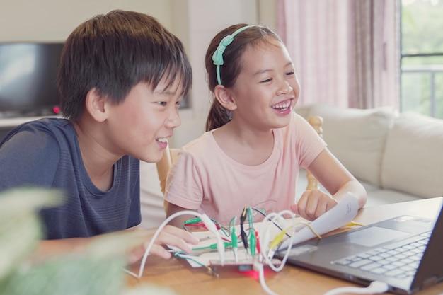 Razza mista giovani bambini asiatici che si divertono imparando a programmare insieme, imparando da remoto a casa, scienza stem, istruzione homeschooling, distanza sociale, concetto di isolamento