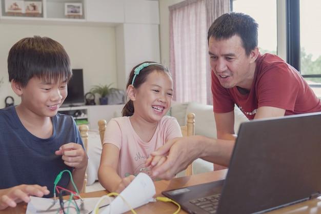 Razza mista giovani bambini asiatici che imparano a programmare con il padre, imparano da remoto a casa, scienza stem, educazione homeschooling, distanza sociale, concetto di isolamento