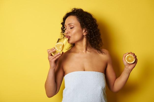 Una giovane donna di razza mista, avvolta in un asciugamano, tiene in mano una fetta di limone e beve acqua di agrumi da un bicchiere