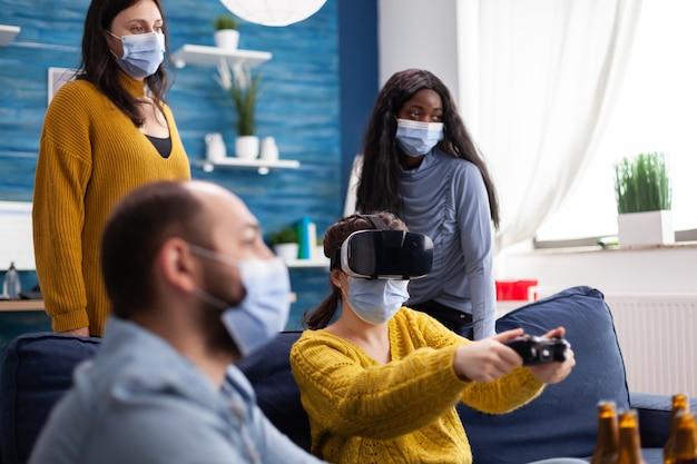 Amici di razza mista in soggiorno che partecipano a una competizione di videogiochi vivendo la realtà virtuale mantenendo le distanze sociali indossando maschere per prevenire la malattia da covid. persone diverse in una nuova festa normale