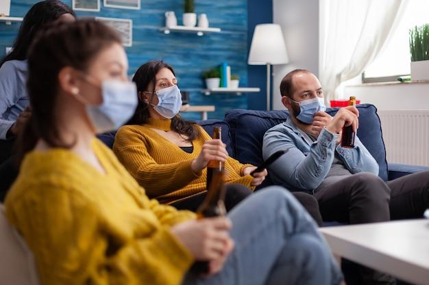 Amici di razza mista che guardano un film sdraiato sul divano indossando una maschera facciale per prevenire l'infezione da covid19 durante la pandemia sociale bevendo birra con il telecomando.