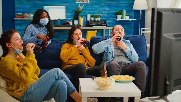 Persone di razza mista che guardano la tv, socializzano, esultano bottiglie di birra che si godono il tempo insieme rispettando il distanziamento sociale indossando maschere di protezione contro il virus covid 19. rilassarsi alla nuova festa normale