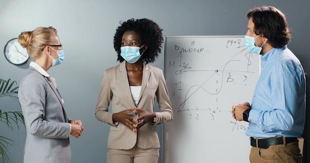 Donne e uomini di razze miste in msks medici che discutono del concetto di studio in aula con la scheda di formule di matematica o fisica sullo sfondo. maschio e femmine multietnici che parlano in ufficio sulla crescita del business