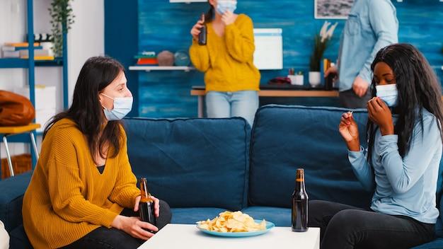 Donne di razza mista sedute sul divano che discutono di togliersi la maschera protettiva mangiando spuntini con in mano bottiglie di birra trascorrendo del tempo alla nuova festa normale
