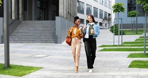 Giovani femmine graziose di razza mista, migliori amiche che parlano allegramente e camminano con tazze di caffè da asporto e per le strade della città. studenti di belle donne felici multietniche che passeggiano fuori con le bevande.